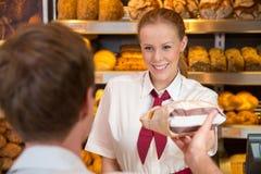 女推销员在卖面包的面包师的商店对顾客 库存图片