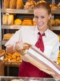女推销员在卖面包的面包师的商店对顾客 库存照片