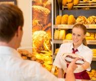 女推销员在卖面包的面包店对顾客 免版税库存照片