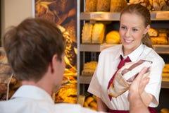 女推销员在卖面包的面包店对顾客 免版税库存图片