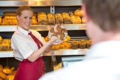 女推销员在提出面包的面包店对顾客 免版税库存照片
