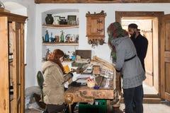 女推销员在老市Sighisoara为纪念品店的顾客服务在罗马尼亚 免版税库存照片