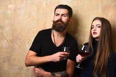 女朋友和男朋友有好奇面孔的喝酒和科涅克白兰地 免版税库存照片