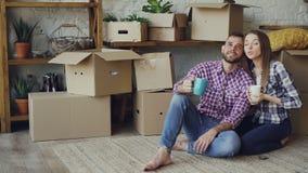 女朋友和男朋友谈话做计划坐新的被购买的公寓地板,看和 股票录像