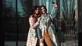 女朋友在一个手机做selfie在城市 股票录像