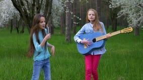 女朋友在梳子获得乐趣并且唱歌在话筒 两个小可爱的女孩无所事事演奏吉他音乐的舞蹈 股票录像