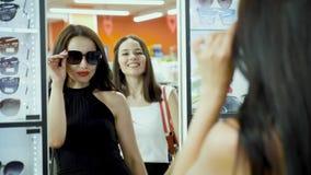 女朋友在镜子前面选择太阳镜,尝试在他们 股票视频