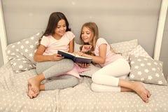 女朋友或姐妹一起放置床读的书 孩子准备上床 宜人的时间舒适卧室 女孩长发 免版税库存照片