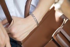 女服不锈钢镯子和棕色袋子 免版税图库摄影
