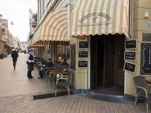 女服务员与顾客谈话在室外咖啡馆在格罗宁根荷兰镇  免版税库存图片