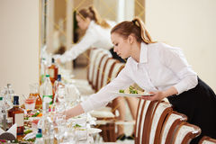 女服务员在承办酒席工作在餐馆 免版税库存照片