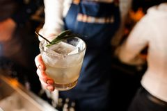 女服务员在拿着与冷的饮料的一条白色衬衣和蓝色围裙穿戴了一块玻璃 库存图片