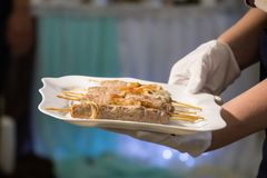 女服务员拿着与饮食kebab的一个盘在棍子 免版税库存图片