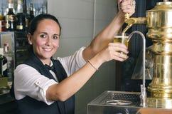 年轻女服务员服务桶装啤酒 库存照片