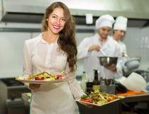 女服务员用在厨房的食物 免版税库存图片