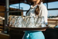 女服务员运载有玻璃的盘子 库存照片