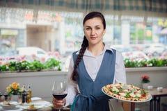 女服务员运载薄饼andd杯红葡萄酒在restautant 免版税库存图片