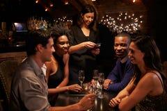 女服务员采取餐馆的比尔付款数字式片剂的 库存照片