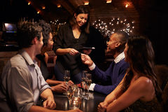 女服务员采取餐馆的比尔付款数字式片剂的 免版税库存图片