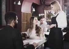女服务员年轻夫妇的服务膳食在桌上 库存照片