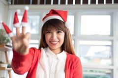女服圣诞老人帽子显示三个手指 亚洲女性穿戴丝毫 免版税库存照片