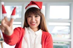 女服圣诞老人帽子显示两个手指 亚洲女性穿戴白色 免版税图库摄影