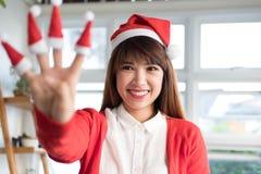 女服圣诞老人帽子显示四个手指 亚洲女性穿戴白色 库存图片