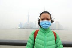 女服在污染城市的一个面具 图库摄影