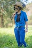 女服帽子和运载她的在草地的吉他 免版税库存图片