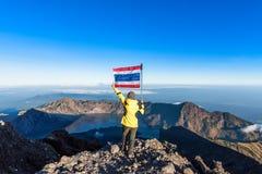 女服黄色站立在Rinjani山顶部的黑色夹克和在结束暴涨以后享用火山、湖和明白蓝天 免版税图库摄影