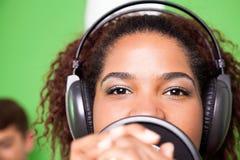 女歌手佩带的耳机,当执行时 免版税库存照片