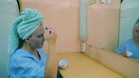 女演员在化装室在镜子前面的一张桌上应用在她的面孔的泥面具与刷子 配置文件 影视素材
