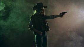 女牛仔在她的手和瞄准上恶棍拿着一把左轮手枪 黑烟背景 慢的行动 侧视图 股票录像