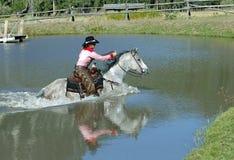 女牛仔横穿池塘反映 免版税库存照片