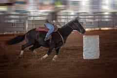 女牛仔骑马以在赛跑竞争的圈地桶的速度 免版税图库摄影