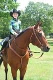 年轻女牛仔坐短距离冲刺的马 免版税库存图片