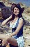 女牛仔妇女微笑愉快在帽子 免版税库存照片