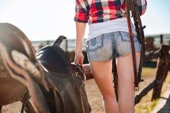 年轻女牛仔简而言之马鞍为乘驾做准备 免版税图库摄影