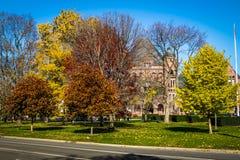 女王的秋天五颜六色的植被停放与在背景-多伦多,安大略,加拿大的安大略省省议会 库存照片