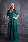 女王/王后、皇家人有冠的,红色头发和绿色礼服 免版税库存照片