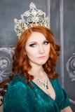 女王/王后、皇家人有冠的,红色头发和绿色礼服 库存照片