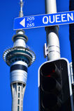 女王/王后反对天空塔的路牌在奥克兰,新西兰 免版税库存照片