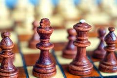 女王/王后和国王前景的 棋盘和棋子,在棋枰的木棋子彩色照片  库存照片