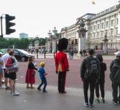 女王/王后` s皇家卫兵横穿路白金汉宫外在伦敦,英国 库存照片