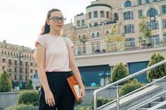 女生16,17岁室外画象  玻璃的女孩,与背包,课本 背景城市晚上街道 免版税图库摄影