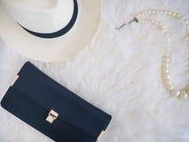 女用无带提包在白色毛皮背景的帽子和珍珠项链 库存图片
