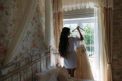 女用贴身内衣裤的后方viev新娘在婚礼前的早晨 新娘的白色便服,为婚礼做准备 免版税库存图片