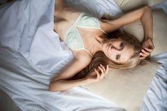 女用贴身内衣裤的女孩在床上睡觉在早晨,白色 免版税库存图片