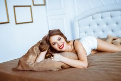 女用贴身内衣裤的女孩在床上 免版税库存图片