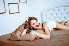 女用贴身内衣裤的女孩在床上 库存图片